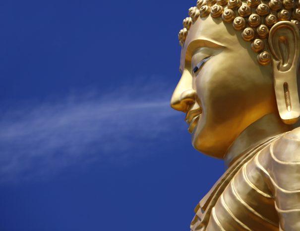 """Golden Buddha statue against blue sky. Chalong, Phuket Thailand."""